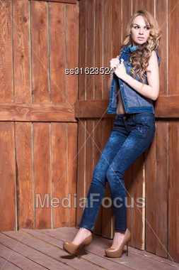 Beautiful Blonde Wearing Jeans Suit Posing Near Wooden Wall Stock Photo
