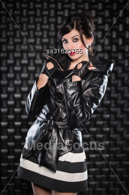 Beautiful Brunette Posing In Black Jacket And Striped Skirt Stock Photo
