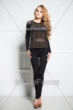 Beautiful Curly Blond Woman In Black Clothes Posing Near White Wall Stock Photo