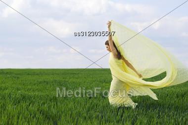 Beautiful Girl Dancing In A Green Field Stock Photo