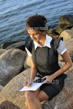 Beautiful Girl With A Notebook And A Calculator Sitting On The Rocks Stock Photo