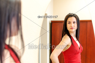 Beautiful Girl In Red Dress Posing In Front Of A Mirror Stock Photo