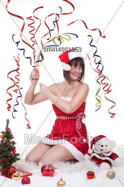 Beautiful Girl Wearing Christmas Dress And Hat Exploding Cracker Stock Photo