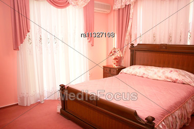 Beautiful Pink Bedroom With Luxurious Curtains Stock Photo