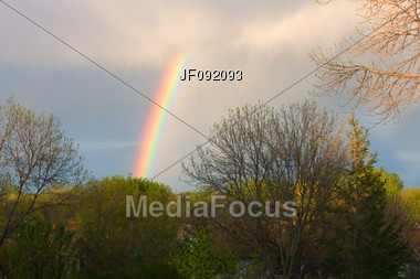 Beautiful Rainbow Coming Down From The Clouds During A Passing Storm Stock Photo