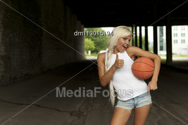 Beautiful Smiling Girl Standing With A Basketball In The Street, Thumbs Up Stock Photo