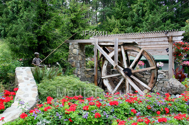Beautiful Springtime Flower Garden And Waterwheel Sculpture Stock Photo