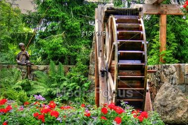 Beautiful Springtime Flower Garden And Waterwheel Sculpture Stock Photo