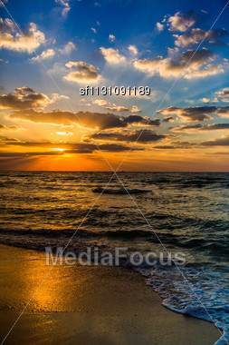 Beautiful Sunset At The Beach, Amazing Colors, Light Beam Shining Through The Cloudscape Over The Arabian Gulf Seascape, United Arab Emirates. Dubai Sea And Beach Stock Photo