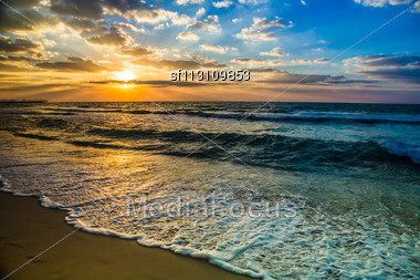 Beautiful Sunset At The Beach, Amazing Colors, Light Beam Shining Through The Cloudscape Over The Arabian Gulf Seascape, United Arab Emirates. Dubai Sea And Beach Stock Photo