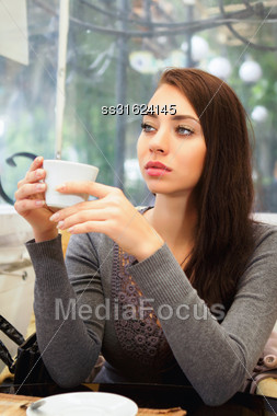 Beautiful Thoughtful Lady Posing With A Cup In The Restaurant Stock Photo