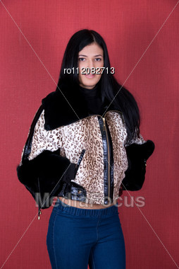 Beautiful Woman In A Leopard Jacket On A Red Background Stock Photo