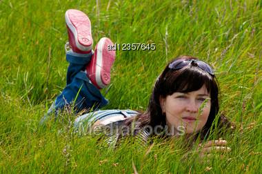 Beautiful Woman Lying On Green Grass Stock Photo