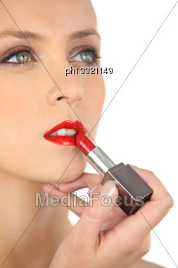 Beautiful Woman Putting On Some Lipstick Stock Photo
