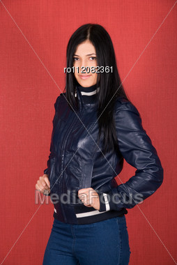 Beautiful Woman In A Red Jacket On A Red Background Stock Photo