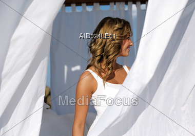 Beautiful Woman Standing Behind White Curtains Stock Photo