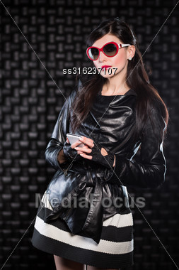 Beautiful Woman Wearing Black Leather Jacket And Red Sunglasses Posing In The Studio With A Mobile Phone Stock Photo