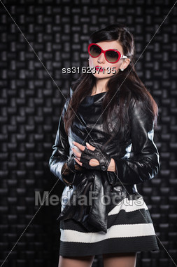 Beautiful Woman Wearing Black Leather Jacket And Red Sunglasses Posing In The Studio Stock Photo