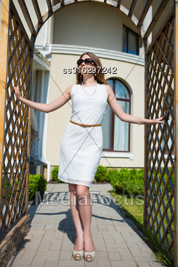 Beautiful Woman Wearing White Dress And Sunglasses Posing In Archway Stock Photo