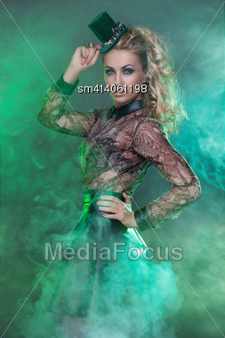 Beautiful Young Blond Woman In Green Fog Wearing Small Hat Stock Photo
