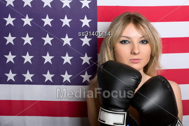 Beautiful Young Blonde With Boxing Gloves On A Background Of The American Flag Stock Photo
