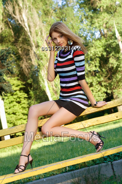 Beautiful Young Blonde Sitting On A Park Bench Stock Photo