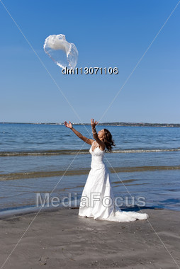Beautiful Young Bride Throwing The Veil Near The Sea Stock Photo