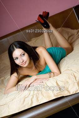 Beautiful Young Brunette Lying On The Bed Stock Photo