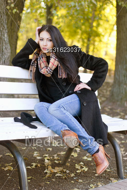 Beautiful Young Brunette Sitting On A Bench In Autumn Park Stock Photo