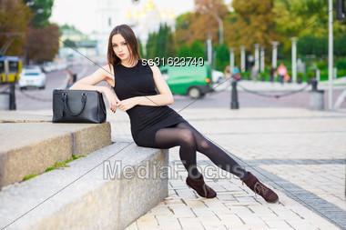Beautiful Young Brunette Wearing Black Dress Posing Near The Road Stock Photo