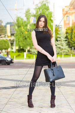 Beautiful Young Brunette Wearing Black Dress Posing With Handbag Stock Photo