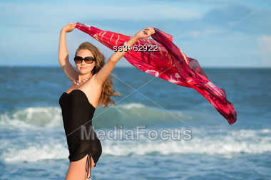 Beautiful Young Lady With Flowered Pareo Posing On The Beach Stock Photo