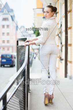 Beautiful Young Lady In White Pants And Jacket Posing Outdoors Stock Photo