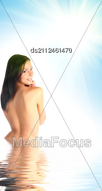 Beautiful Young Woman Half In Water Against Blue Sky And Sun Light Stock Photo