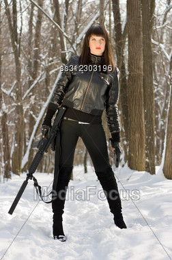 Beautiful Young Woman With A Rifle In Forest Stock Photo