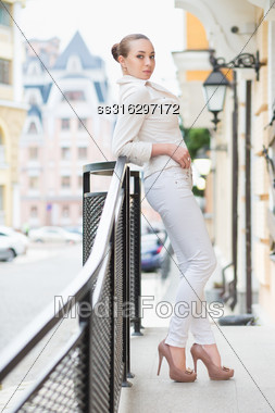 Beautiful Young Woman In White Pants And Jacket Posing Outdoors Stock Photo