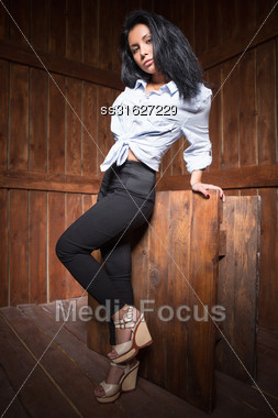 Beautiful Young Woman In White Shirt And Black Pants Posing Near Wooden Wall Stock Photo