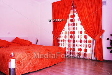 Bedroom With Pink Walls, Red Curtains And Bedspread. Stock Photo