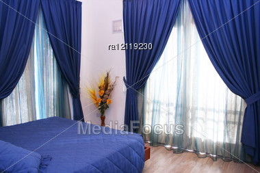 Bedroom With Blue Curtains And Bedspread. Stock Photo