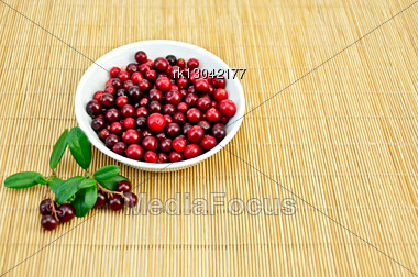Berry Lingonberry In A White Porcelain Bowl, Two Twigs With Berries And Green Leaves On A Bamboo Mat Stock Photo