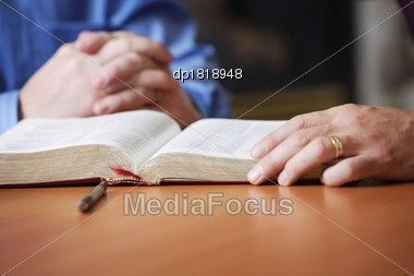 Bible And Praying Hands Stock Photo