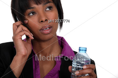 Black Businesswoman On The Phone Waiting To Take A Sip. Stock Photo