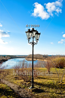 Black Lantern With Three Lights On The Background Of Blue Sky, Paths, Grass, Trees And Blue Of The River On A Sunny Day Stock Photo