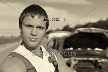 Black And White Portrait Of A Hadsome Mechanic With A Broken Car On Background Stock Photo