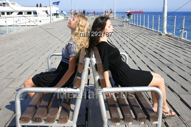 Blond And Brunette Girls On The Bench On The Pier Stock Photo