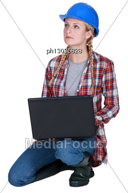 Blond Builder Kneeling With Laptop Stock Photo