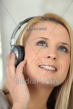 Blond Girl Listening To Music Through Headphones Stock Photo