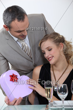 Blond Receiving Gift From Boyfriend At Romantic Dinner Stock Photo