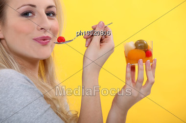 Blond Woman Eating Fruit Cocktail Stock Photo