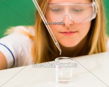 Blond Woman Checking With Measuring Pipette Liquid At Laboratory Stock Photo